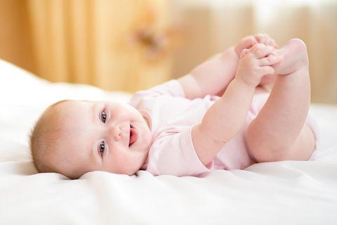Woran erkennen Baby Lebewesen? Baby liegt auf Bett
