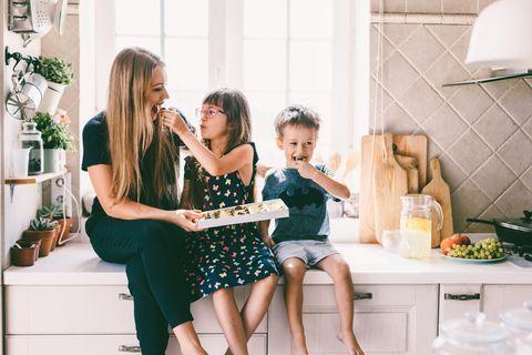Mutter sitzt mit zwei Kindern in Küche