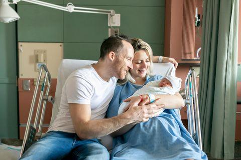 Glückliche Eltern halten ihr Neugeborenes in den Armen