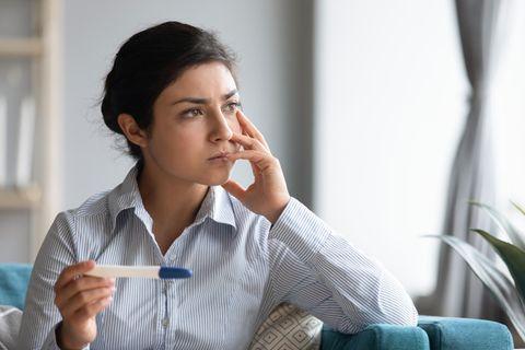 hCG-Tabelle: Frau mit Schwangerschaftstest