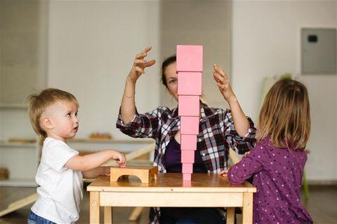 Sichere Kita: Zwei Kinder spielen mit ihrer Betreuerin