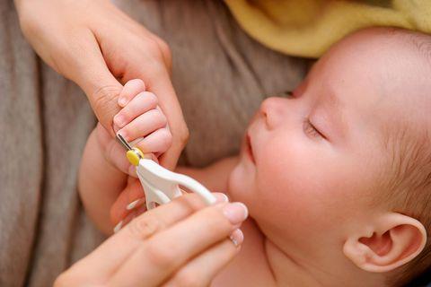 Einem Baby werden mit einer Nagelschere die Fingernägel gekürzt