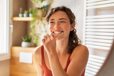 junge Frau putzt sich im Badezimmer die Zähne