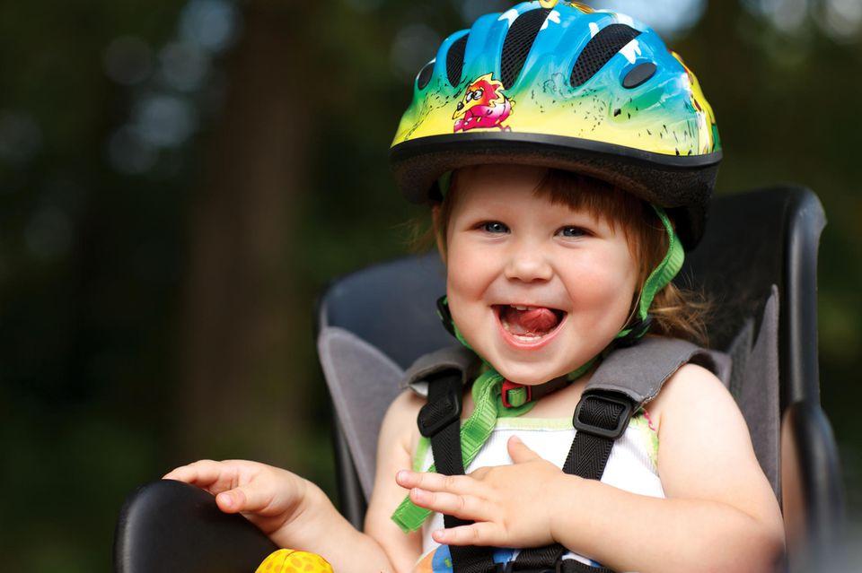 Kinderfahrradhelm im Test: Kleines fröhliches Mädchen mit buntem Helm auf Fahrradsitz.