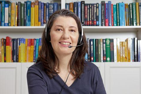 Frau mit Headset vor Bücherregal