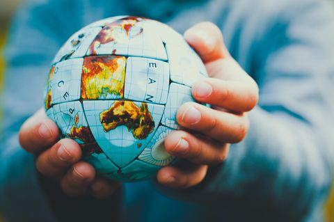 Kindererziehung weltweit: Kind hält Weltkugel in der Hand