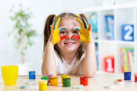 Ein kleines Mädchen malt mit Fingerfarben.