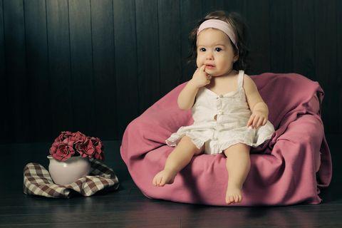 Ein Baby liegt auf dem Bauch und lächelt in die Kamera