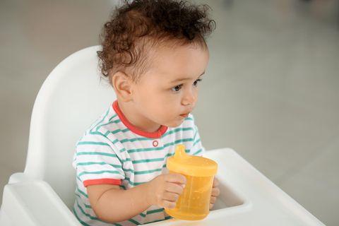 Ein Kleinkind sitzt in einem Babystuhl und hält einen gelben Trinkbecher in den Händen