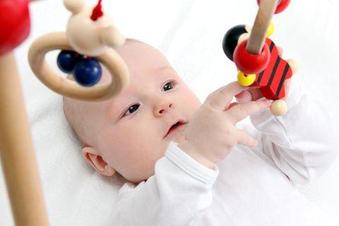 Ein Baby liegt unter einem Spielbogen und spielt mit dem daran befestigten Greifspielzeug.