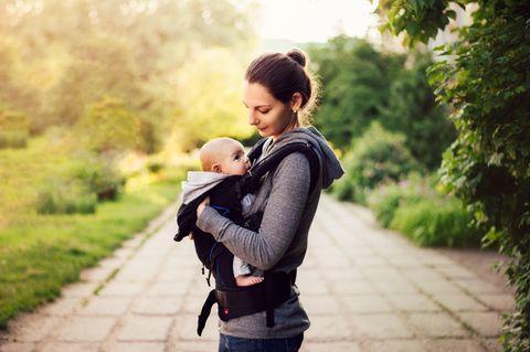 Ein Mann hat ein Kleinkind in der Tragehilfe vor der Brust und hält eine Frau an der Hand als die Spitze eines Berges erreichen.