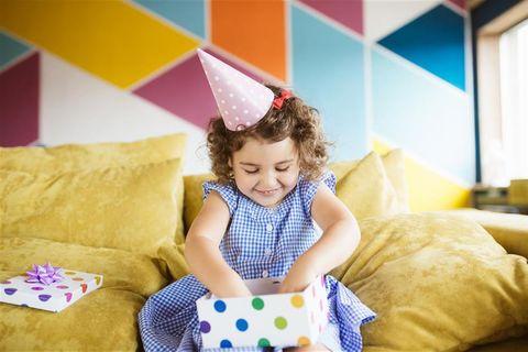 Geschenkideen für Kinder: Kleines Mädchen packt Geschenk aus