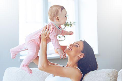 Ein Frau hebt ihr Kind hoch, das sich sehr freut und lacht.