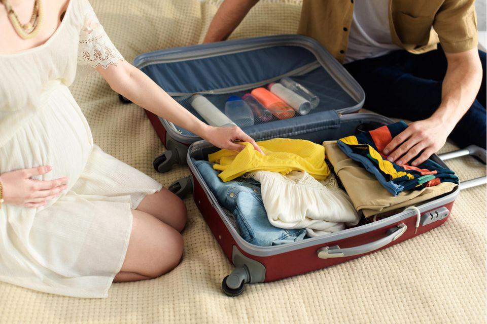 Eine schwangere Frau und ein Mann packen einen Koffer.