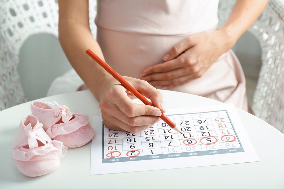 Eine schwangere Frau macht mit einem Filzstift eine Strichliste auf ihren Babybauch.