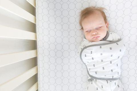 Ein Baby liegt in einem Babyschlafsack mit geschlossenen Augen im Bett.