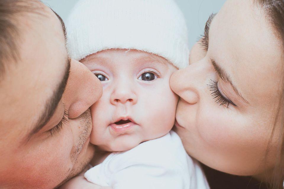 Eltern küssen ihr Neugeborenes