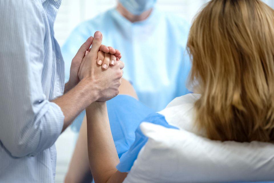 Ein Mann hält einer Frau die Hand während sie gebärt.