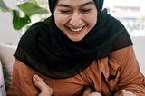 Postpartum Unfiltered: Frau lächelt Baby an