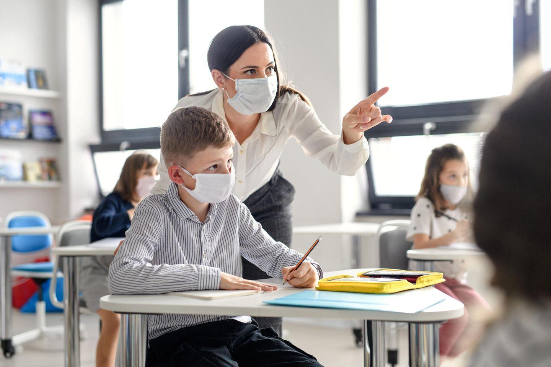 Impffrage: Lehrerin erklärt Schüler etwas
