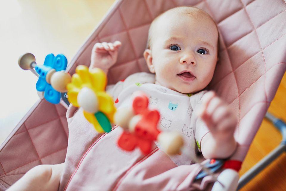 Babywippe im Test: Baby sitzt in rosa Wippe mit bunter Spielzeugkette vor sich.