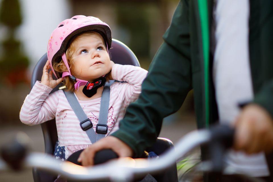 Kinderfahrradsitz-Test: Kleines Mädchen mit rosa Helm lässt sich im Kindersitz auf Papas Fahrrad schieben.