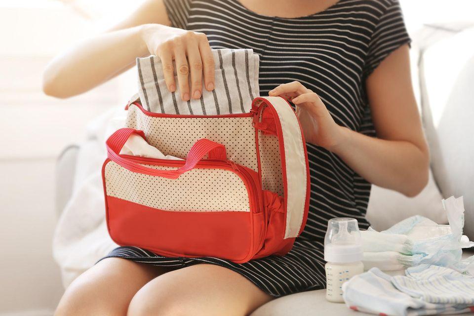 Wickeltasche packen: Mutter packt Windeln, Fläschchen und Stofftuch in die Tasche.