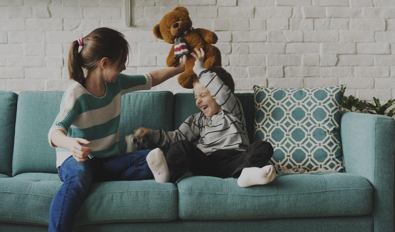 Geschwister spielen mit Teddy