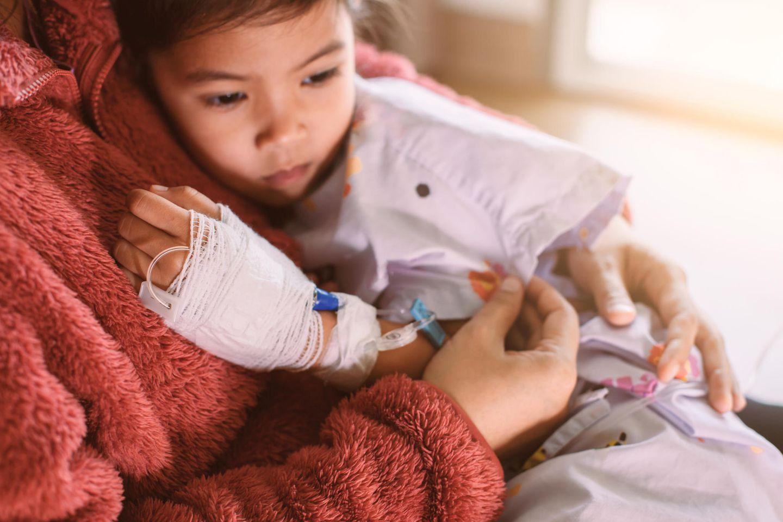 Kleines Mädchen mit Kanüle in der Hand kuschelt sich an ihre Mama