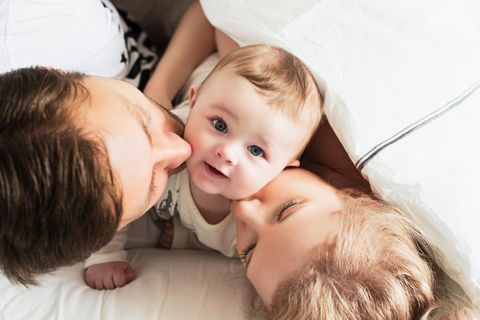 Ein Mann und eine Frau geben ihrem Kind einen Kuss auf die Wangen während das Kind nach oben in die Kamera schaut.