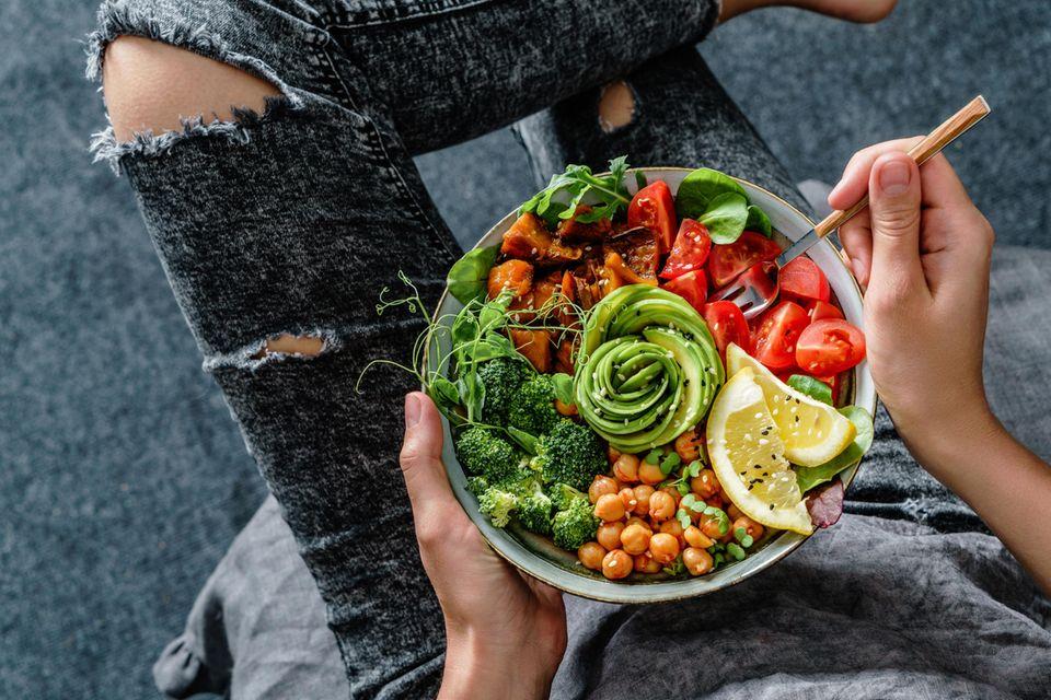 Frau isst Buddha Bowl mit gesunden Lebensmitteln