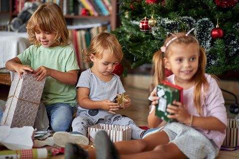Weihnachtsgeschenke für Kinder: Drei kleine Kinder packen unter dem Weihnachtsbaum Geschenke aus.
