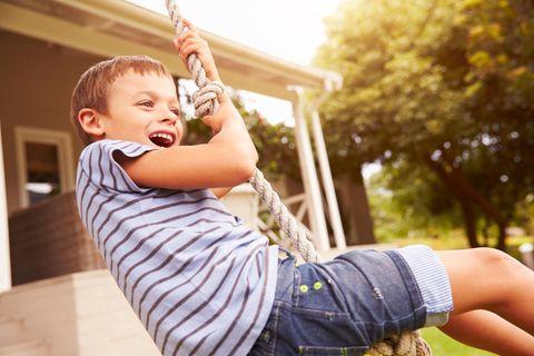 Ein Junge schwingt auf einem Seil und lächelt glücklich
