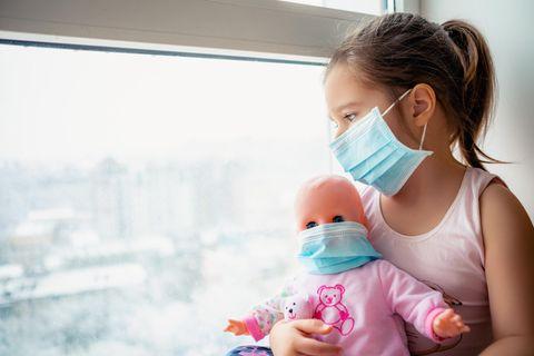 Ein Mädchen und ihre Puppe haben beiden einen Mundnasenschutz auf und schauen traurig aus dem Fenster.