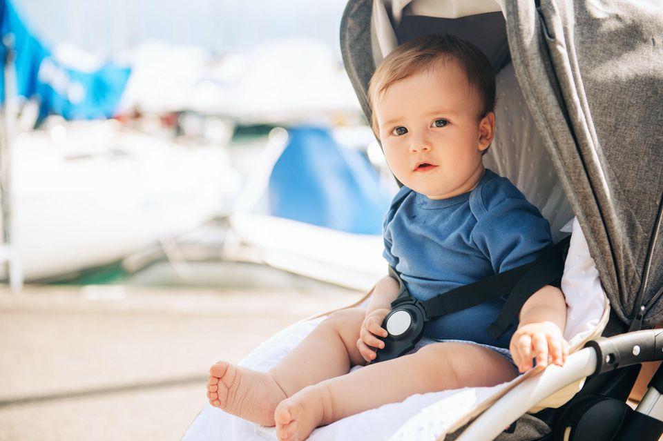 Ab wann in den Buggy: Baby im blauen Body sitzt angeschnallt im Buggy