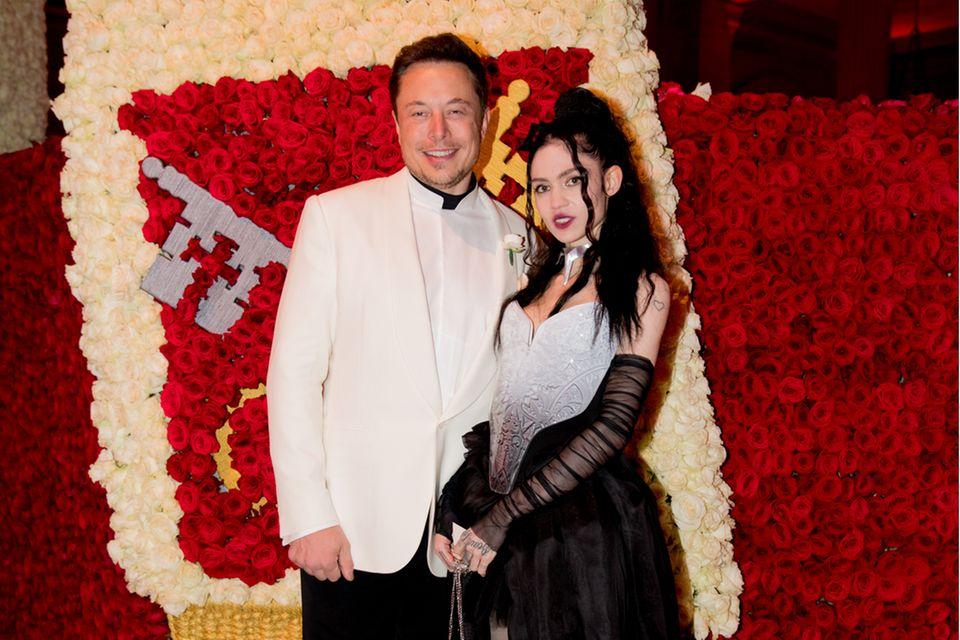 Elon Musk und Grimes posen vor einem Blumengemälde