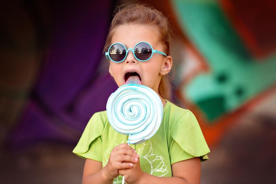Ein Mädchen mit einer blauen Sonnenbrille auf der Nase lutscht an einem großen blauen Lolli.