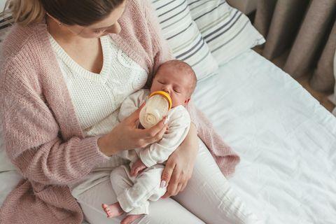 Eine Mutter füttert ihr Neugeborenes mit dem Fläschchen