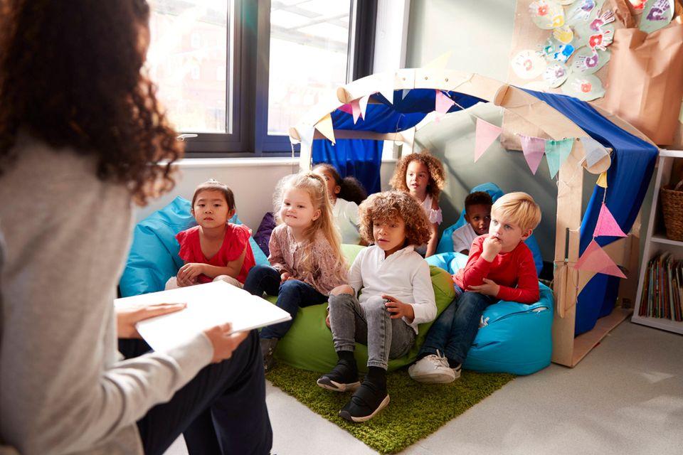 Rassismus: Unterschiedliche Kinder sitzen im Kindergarten beisammen