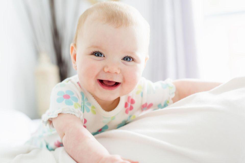 Ein Baby lacht strahlend in die Kamera.