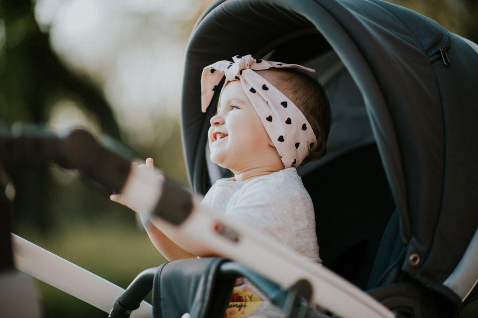 Buggys im Test: Zwei Mütter schieben ihre Kinder in Buggys durch herbstlichen Park.