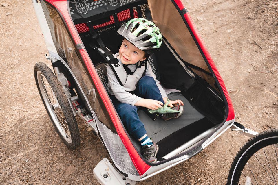 Kinderfahrradanhänger im Test: Junge mit Helm sitzt im Fahrradanhänger