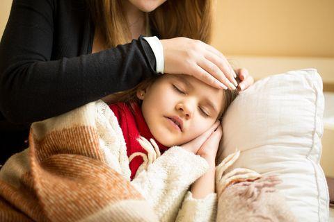 Eine Frau streichelt ihrer kranken Tochter die Stirn.