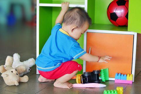 Baby geht in die Hocke, um ein Spielzeug zu greifen