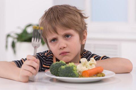 Ein Junge starrt angewidert das Gemüse auf seiner Gabel und seinem Teller an.