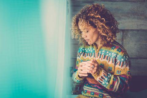 Emotional überfordert: Frau schaut nachdenklich aus dem Fenster