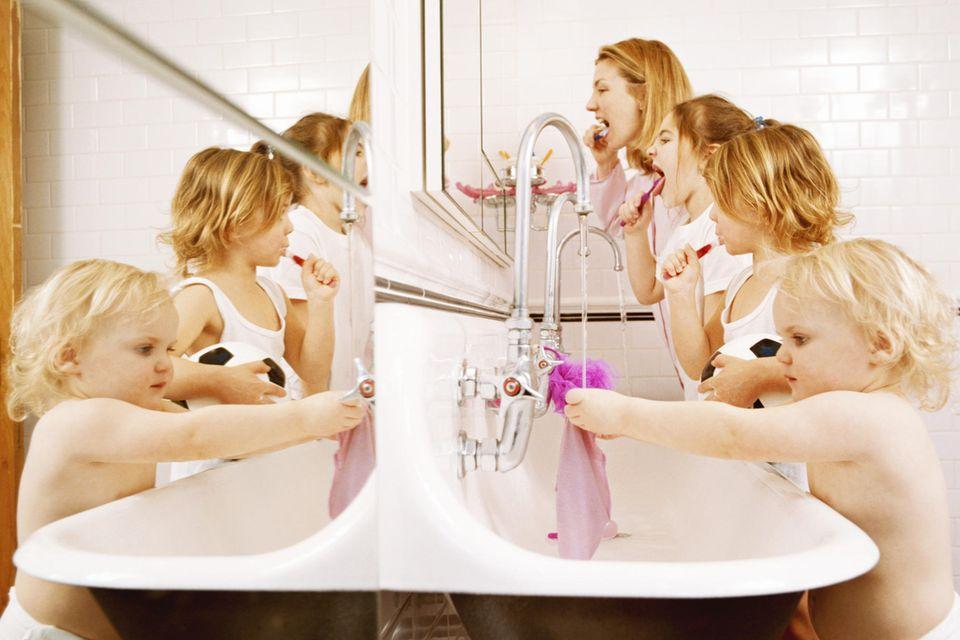 Wassersparen: Mutter mit Kindern putzt sich die Zähne während die Wasserhähne laufen