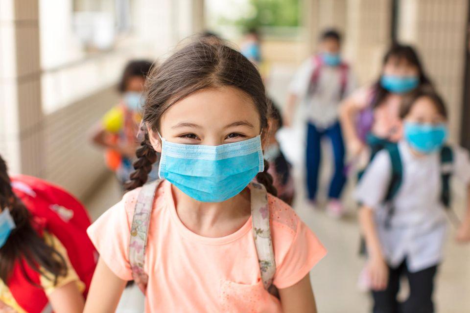 Ein Mädchen mit Mund-Nasen-Schutz läuft auf einem Schulgang mit ihren Mitschülern und lacht in die Kamera.