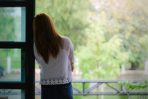 Mit diesen 7 Dingen machst du dir das Leben schwer: Frau schaut nachdenklich aus dem Fenster.