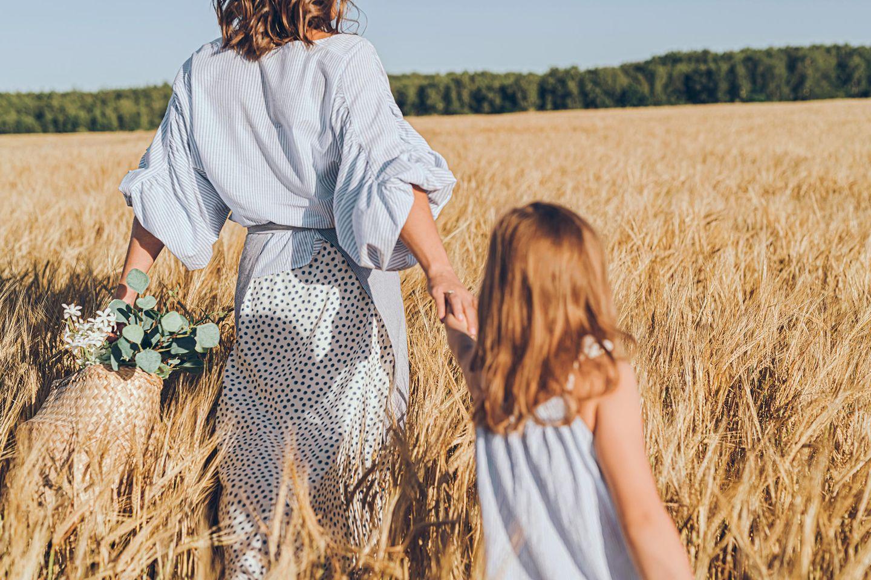 Nachhaltige Promi-Familien: Mutter mit Tochter an der Hand in der Natur